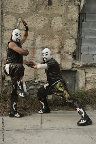 Hispanic men dressed as Mexican wrestlers