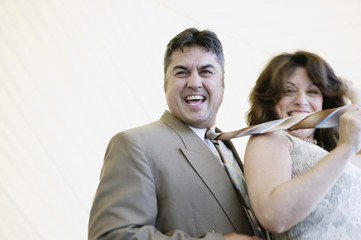 Hispanic woman pulling husband by tie