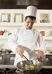 Middle Eastern male chef cooking in kitchen