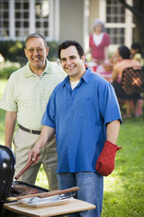 Hispanic father and adult son barbecuing