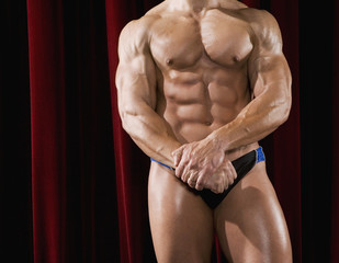 Hispanic male body builder with hands clasped