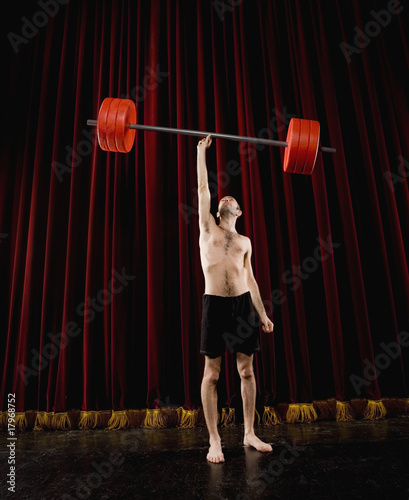 Hispanic man holding barbell with one hand