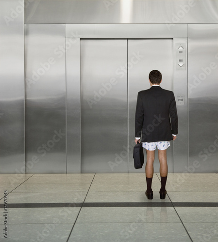 Businessman not wearing pants in front of elevator