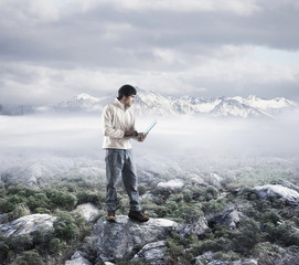 Man holding laptop with mountain range in background