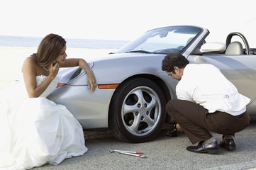 Hispanic newlyweds changing car tire