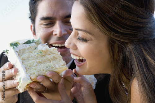 Hispanic newlyweds eating cake