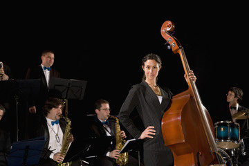 Woman holding upright bass in front of band