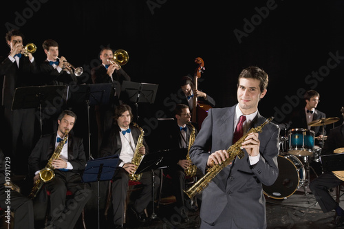 Man holding clarinet in front of orchestra