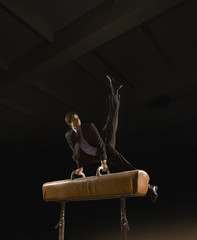 Hispanic businessman performing on pommel horse