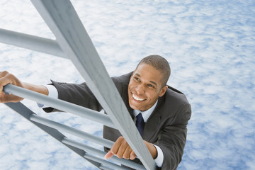 Mixed race businessman climbing ladder into the clouds