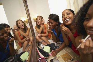 Multi-ethnic group of friends applying makeup