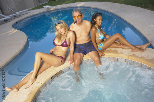 Playboy enjoying hot tub with young girlfriends