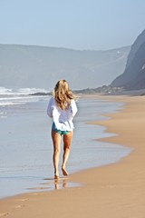 Young blonde woman jogging at the beach