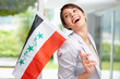 Cute woman laughing while holding an Iraqi flag , looking away