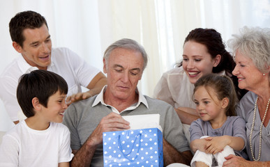 Family giving to grandfather a present