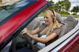 Woman Driving Convertible Car Talking on Bluetooth Headset poster
