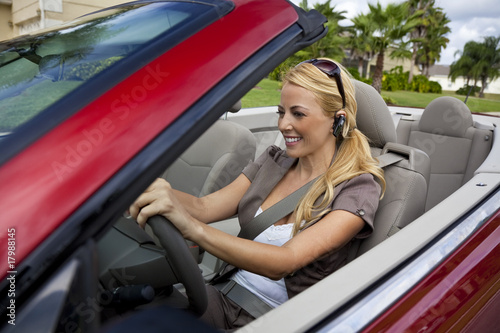 Woman Driving Convertible Car Talking on Bluetooth Headset