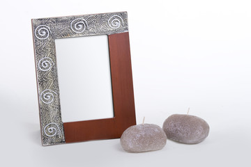 stylish photo frame with some candles laying by it
