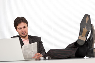 Young modern businessman with laptop and newspaper