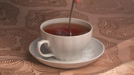fill  sugar in a cup tea and stirring by its teaspoon.