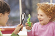 Boy and girl (8-9) with magnifying glass