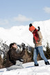 Young man photographing young woman holding snowball  in winter scene