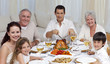 Family eating turkey and vegetables in a celebration meal