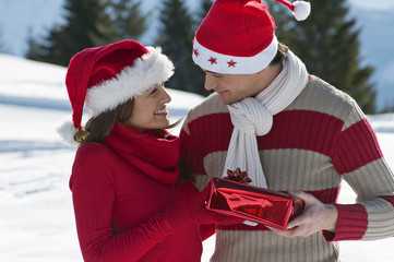 Couple in Christmas outfit, giving a present