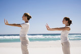 Two women exercising yoga on beach, side view