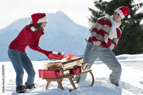 Couple with sleigh and presents in winter scene