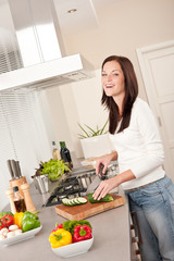 Smiling happy woman cutting zucchini in the kitchen