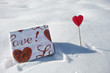 Present and lollipop with hearts in the snow
