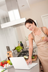 Cheerful woman with glass of champagne and laptop