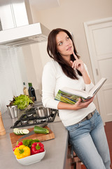 Beautiful woman holding cookbook in the kitchen