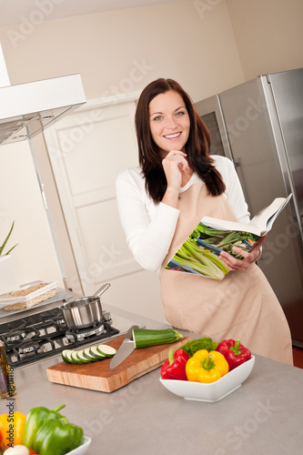 Smiling woman holding cookbook in the kitchen