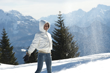 Young woman in winter scene with snow spray, arms outstretched