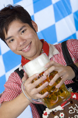 Smiling Asian holds Oktoberfest beer stein (Mass) - Mann mit Maß
