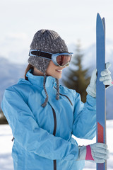 Young woman with skis and ski shades