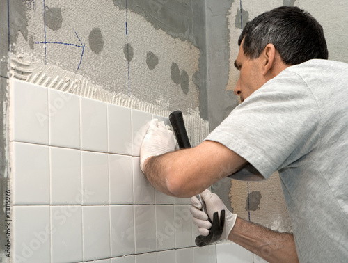 Man Tiling A Bathroom Wall