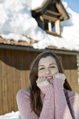 Young woman in front of ski lodge