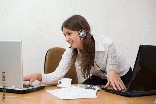 Young businesswoman at the desk with two laptops