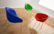Three empty, colorful chairs in an empty room
