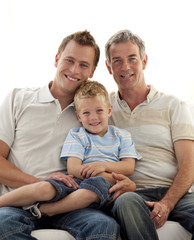 Smiling son, father and grandfather sitting on sofa
