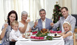 Family tusting in a Christmas dinner with white wine
