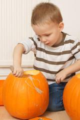 little boy having fun with pumpkin