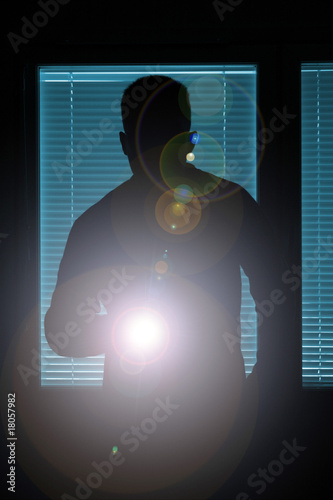 Silhouette of a man pointing with flashlight