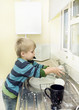 Child plays with soap and water at the kitchen sink.