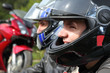 portrait of two motorcyclists sitting on country road near bike