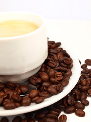 Cup of coffee with coffee beans isolated on white