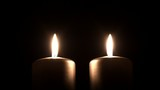 Two silver colored candles burning with a dark background